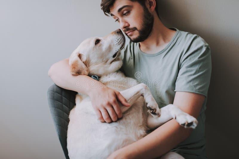 Taille omhoog van een jonge mensenzitting als voorzitter met zijn hond royalty-vrije stock afbeelding
