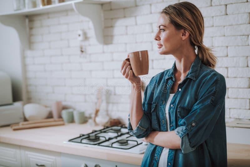 Taille omhoog van kalme vrouw die de afstand in haar keuken onderzoeken royalty-vrije stock afbeeldingen