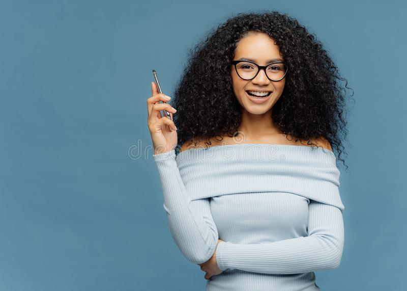 Taille omhoog van mirthful Afro wordt de geschoten de Amerikaanse vrouw smartphone houdt, wacht op vraag, geniet van prettig gesp royalty-vrije stock afbeeldingen
