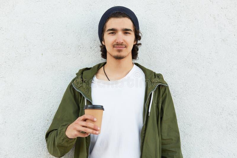 Taille omhoog van modieuze tiener met culry donker haar wordt de geschoten, draagt modieuze hoed en het groene jasje, houdt meene royalty-vrije stock fotografie