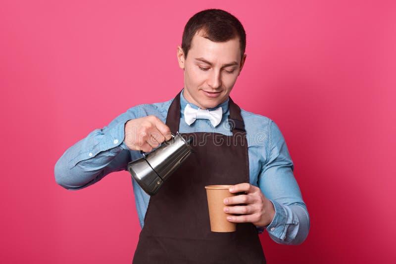 Taille omhoog van professionele mannelijke barista wordt de geschoten giet koffie van koffiezetapparaat in document kop, draagt o stock afbeelding