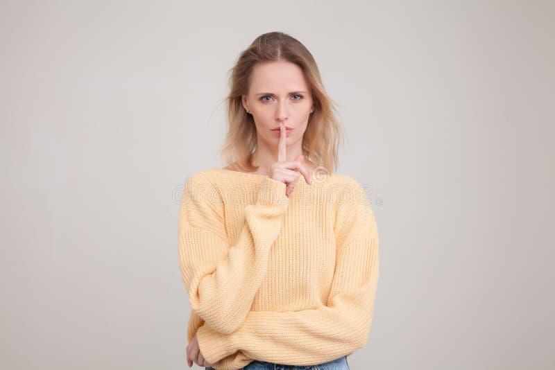 Taille-op portret ga jonge blonde vrouw die stilteteken met ernstige gezichtsuitdrukking tonen het vragen om haar geheim aan iede royalty-vrije stock fotografie