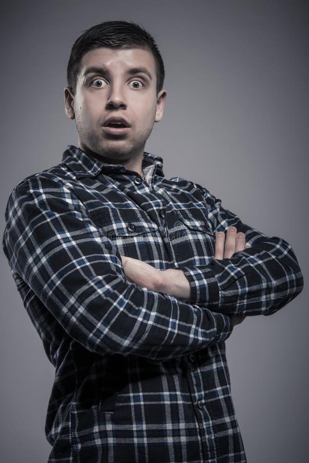 Portret van de verraste mens in gecontroleerd overhemd met gekruiste wapens stock foto