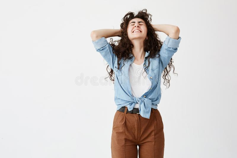 Taille-op portret van emotioneel donker-haired vrouwelijk model draagt denimoverhemd dichtklemt haar witte zelfs tanden in vreugd stock foto's