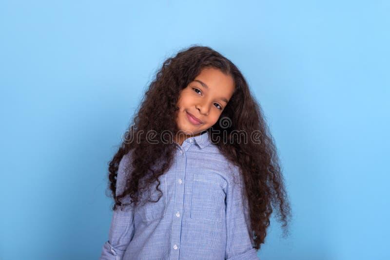 Taille op portret van glimlachend mulatta kroes- meisje op een blauwe achtergrond met exemplaarruimte stock foto's
