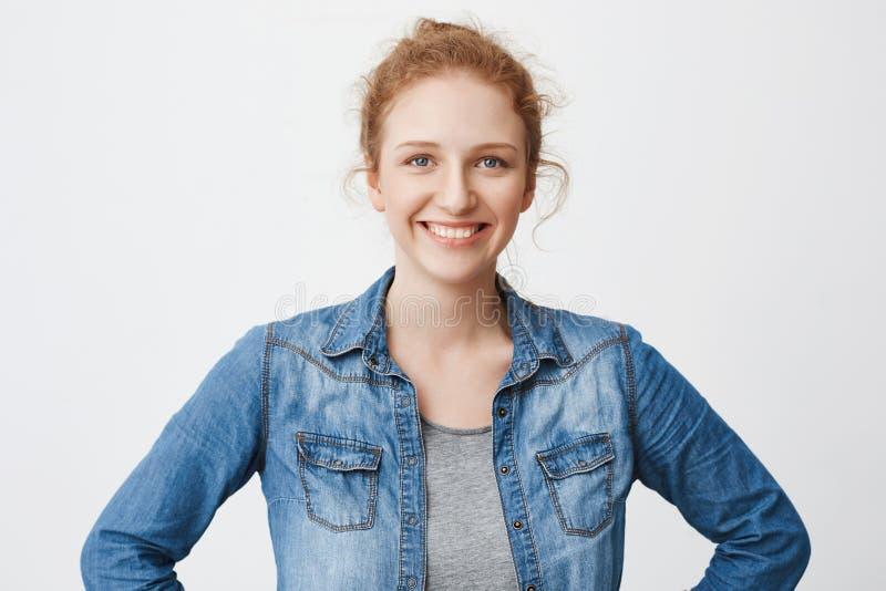 Taille-op portret van leuk gelukkig Europees die roodharigemodel met haar in de handen van de broodjesholding op taille en het be stock afbeelding