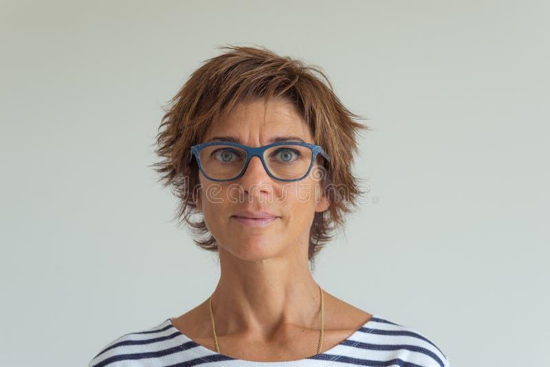 Taille op portret van volwassen vrouw met rode haren, groenachtig blauwe ogen, oogglazen en vrolijke gelaatsuitdrukking, op neutr royalty-vrije stock foto's