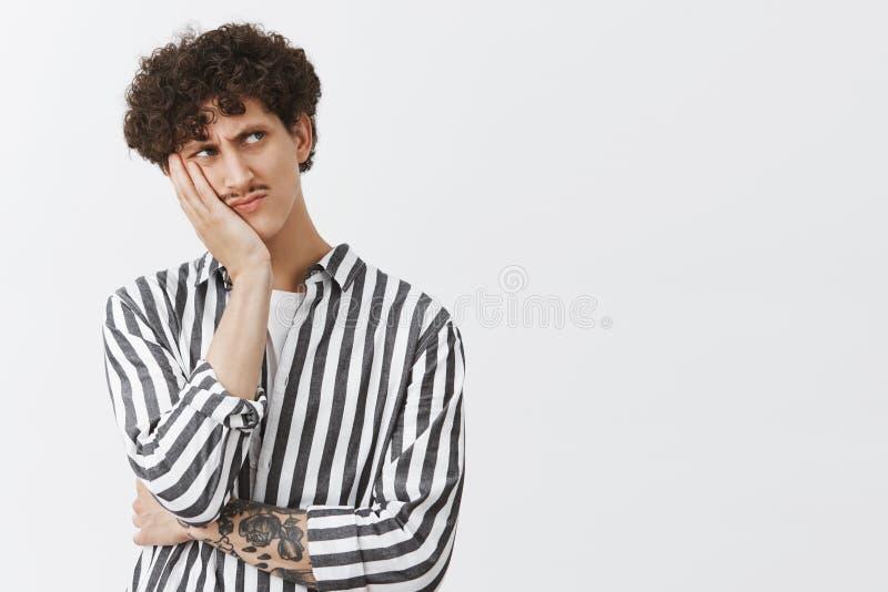 Taille-op schot van betrokken ongelukkig en somber jong mannetje met snor krullend kapsel en tatoegeringen die gezicht op palm le stock afbeelding
