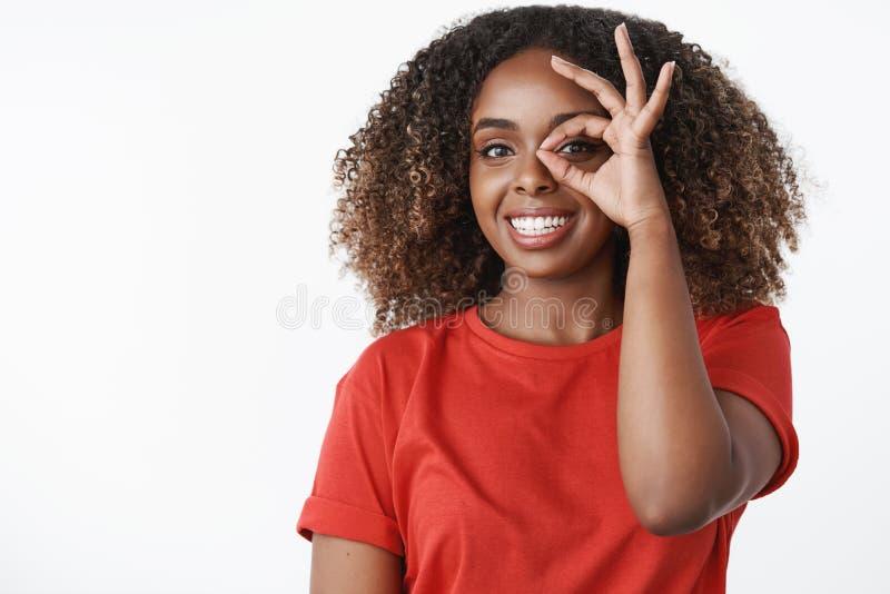 Taille-op schot van charismatische en gelukkige jonge optimistische vrouwelijke vrijwilliger in rode t-shirt die ruim en o.k. gli stock afbeeldingen