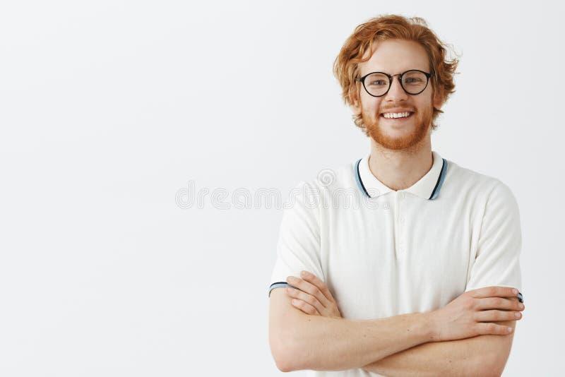 Taille-op schot van creatieve zekere en succesvolle mannelijke ondernemer in wit polooverhemd en zwarte glazen met rood haar royalty-vrije stock afbeelding