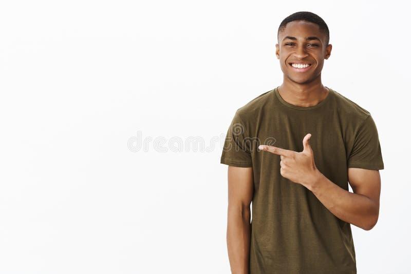 Taille-op schot van de aantrekkelijke charismatische Afrikaanse Amerikaanse mens die product het richten links en het glimlachen  stock foto