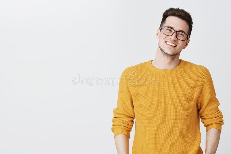 Taille-op schot van de gelukkige en verrukte knappe jonge mens in glazen en geel sweater overhellend hoofd, het glimlachen en het royalty-vrije stock foto