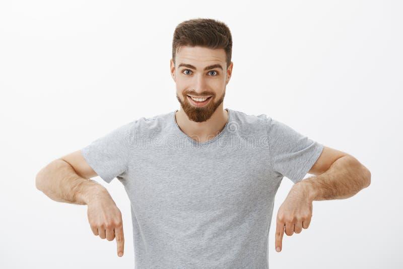 Taille-op schot van de opgewekte en zekere charmante donkerbruine mens met baard en snor die neer en ruim glimlachen bij richten royalty-vrije stock afbeelding