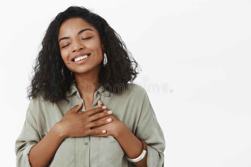 Taille-op schot van dromerig en geraakt teder Afrikaans Amerikaans meisje met de krullende palmen van de kapselholding bij hart h royalty-vrije stock foto