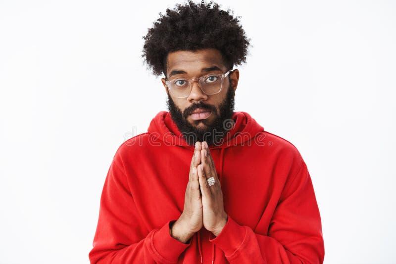 Taille-op schot van ernstig-kijkt Afrikaanse kerel met baard dient de holding bidt zoals vragend om hulp die in behoefte zijn die stock afbeelding