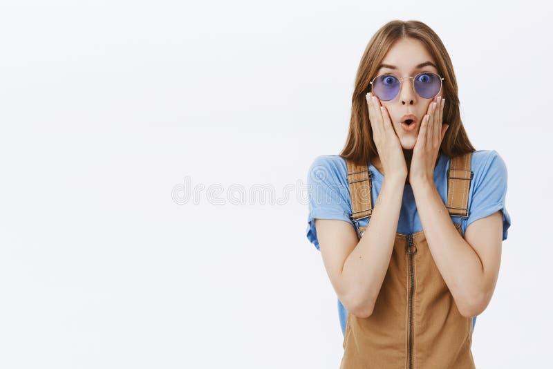 Taille-op schot van geïmponeerd en verrast aantrekkelijk charismatisch wijfje in bruine overall en het blauwe zonnebril vouwen stock afbeelding