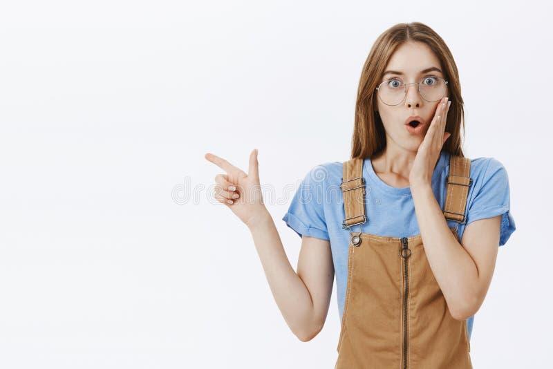 Taille-op schot van geïntrigeerd en verbaasd het charmeren brunette in glazen en bruine overall die wauw wordt gevraagd zeggen en royalty-vrije stock afbeelding