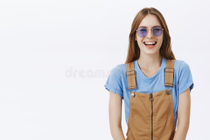 Taille-op schot van het charmeren gelukkig en geamuseerd Europees brunette in bruine overall en modieuze zonnebril die vreugdevol stock foto