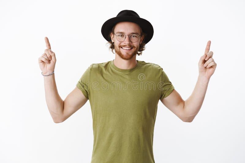 Taille-op schot van knappe gelukkige charismatische roodharige gebaarde kerel in hoed en olijft-shirt die handen opheffen die ben royalty-vrije stock afbeeldingen