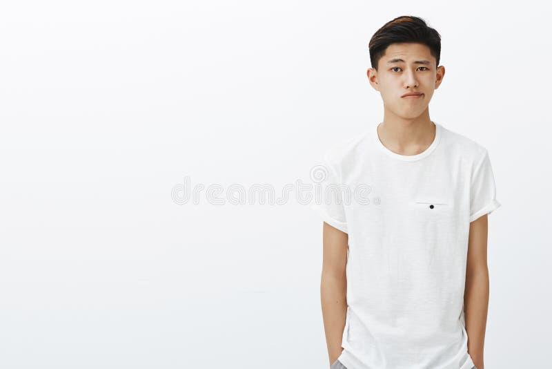 Taille-op schot van knappe modieuze Koreaanse kerel in witte t-shirt dient de holding zakken het smirking in zich bevindt in norm royalty-vrije stock afbeeldingen