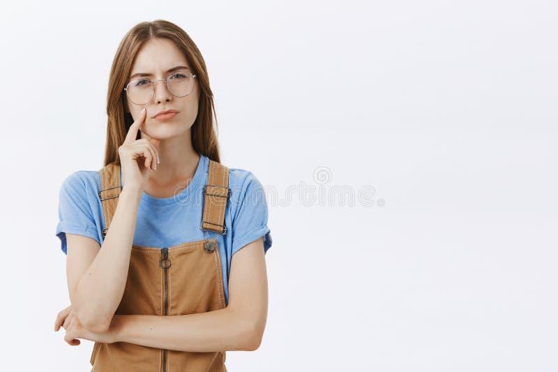 Taille-op schot van nadenkende slimme en intelligente jonge creatieve vrouw met bruin haar in overall en glazen het loensen royalty-vrije stock foto's