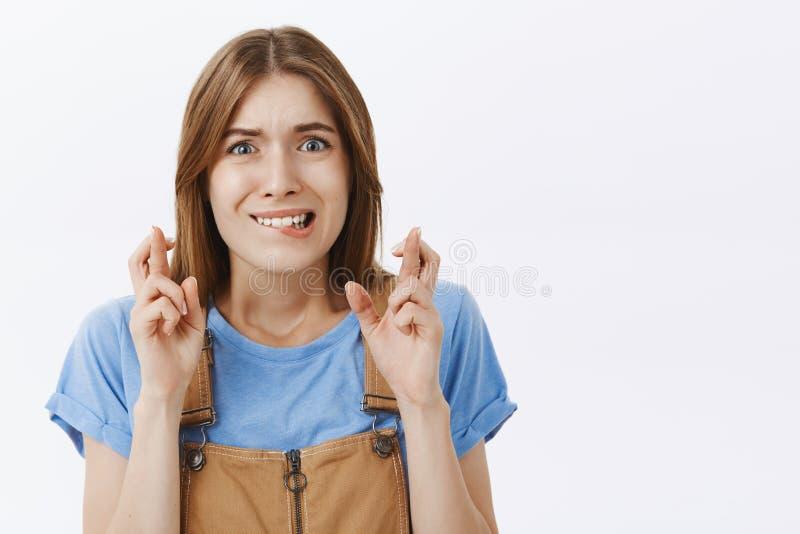 Taille-op schot van ongerust gemaakt bezorgd leuk wijfje met bruin haar in blauwe t-shirt het bijten lagere lip van zenuwen het f royalty-vrije stock afbeeldingen
