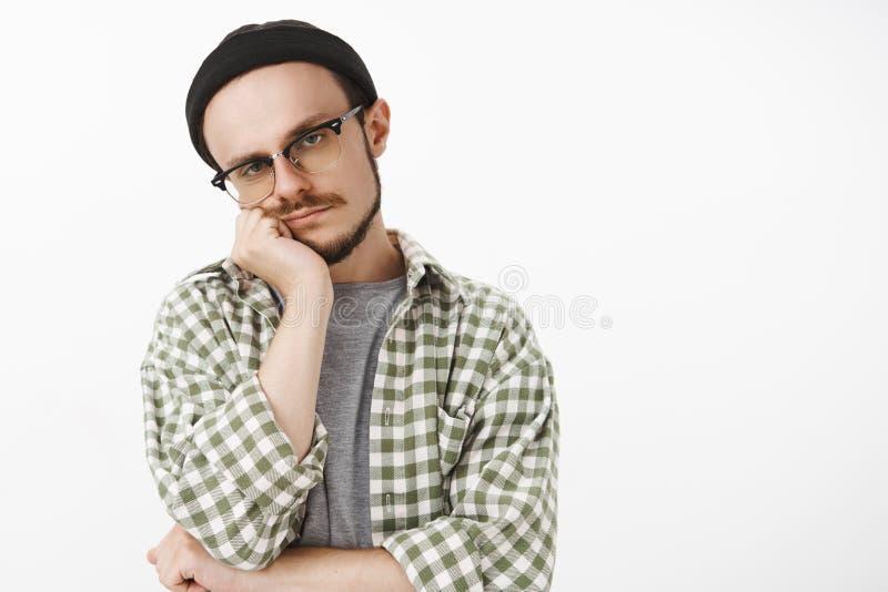 Taille-op schot van onverschillige unemotive bored knappe vrouwelijke student in hipster beanie glazen en gecontroleerd overhemd royalty-vrije stock afbeeldingen