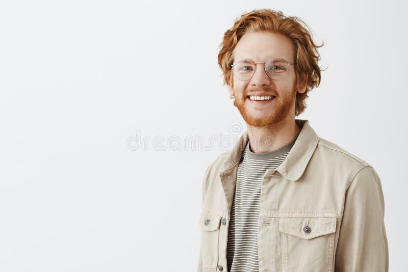 Taille-op schot van prettige knappe roodharige rijpe kerel met baard in transparante glazen en beige jasje over t-shirt royalty-vrije stock fotografie