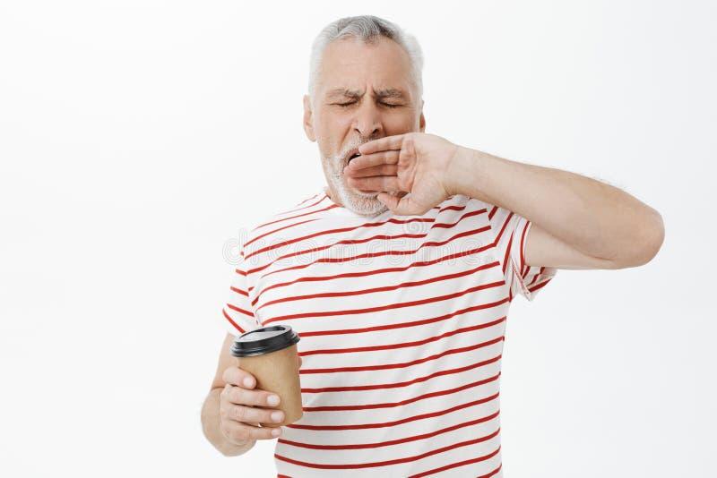 Taille-op schot van slaperige en vermoeide grootvader die met grijs haar met gesloten ogen geeuwen die document kop van koffie ho stock foto