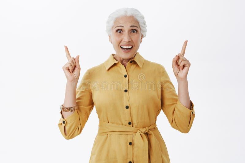 Taille-op schot van verbaasde en opgewekte gelukkige charmante Europese hogere dame die in modieuze trenchcoat wapens opheffen di royalty-vrije stock foto