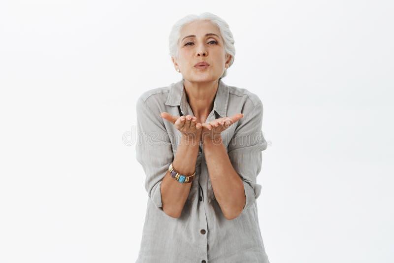 Taille-op schot van vriendelijke en leuke houdende van grootmoeder met grijs haar die lippen vouwen die kus via lucht met palmen  stock foto's