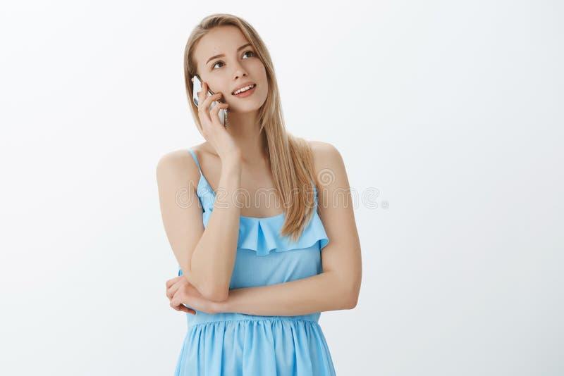 Taille- tirée de charmer la fille attirante de charme dans la robe bleue avec les cheveux blonds parlant en passant avec le smart photo stock