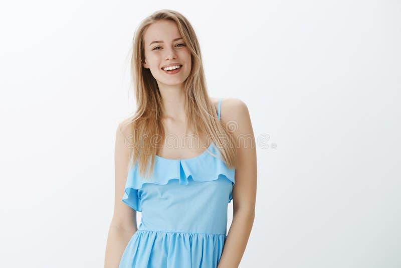 Taille- tirée de l'étudiante élégante attactive sûre et agréable dans la robe bleue posant sincèrement heureux et photo stock