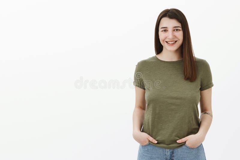 Taille- tirée de la brune lumineuse et sincère belle femelle avec la coiffure courte et le sourire amical grimaçant à photo stock