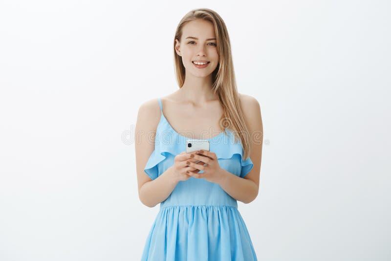 Taille- tirée de la femelle attirante à l'air amical avec les cheveux blonds dans le smartphone bleu de participation de robe et  photographie stock