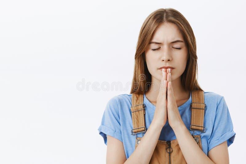 Taille- tirée de la jeune femme fidèle focalisée à l'air sérieux dans le T-shirt bleu semblant déterminé et concentré image libre de droits