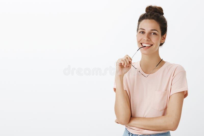 Taille- tirée du cadre acéré sûr de membre de l'équipe féminin heureux et habile des verres en tant que pose joyeux avec l'indivi photo libre de droits