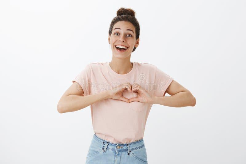 Taille- tirée jeune de la fille enthousiaste et insouciante heureuse avec le petit pain de cheveux montrant le geste de coeur au- images libres de droits