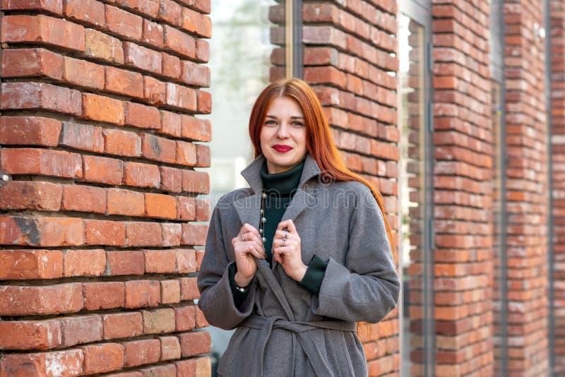 Taille vers le haut de portrait d'une fille avec de longs cheveux rouges magnifiques dans un gra photographie stock