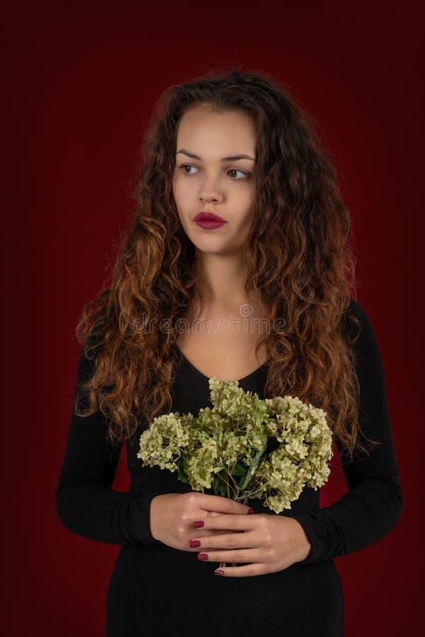 Taille vers le haut de portrait d'une jeune femme avec le long port de cheveux bouclés photographie stock libre de droits