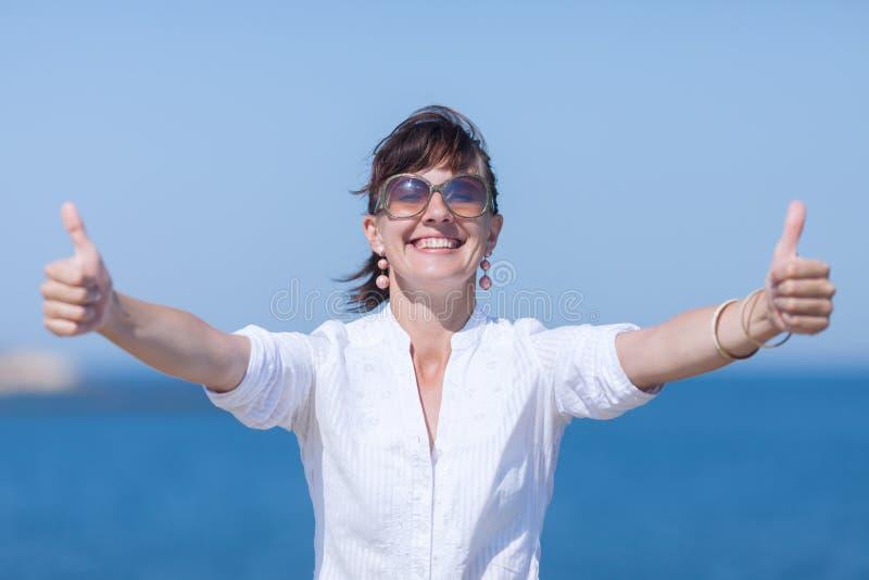 Taille vers le haut de portrait de fille avec des pouces par les deux mains photographie stock libre de droits