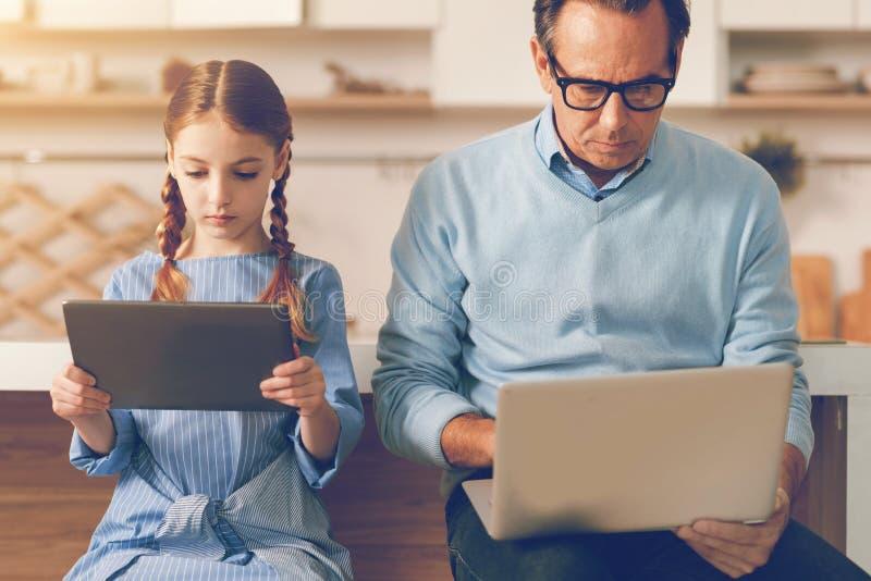 Taille vers le haut de tir de père et de fille absorbés à l'aide des ordinateurs photo stock