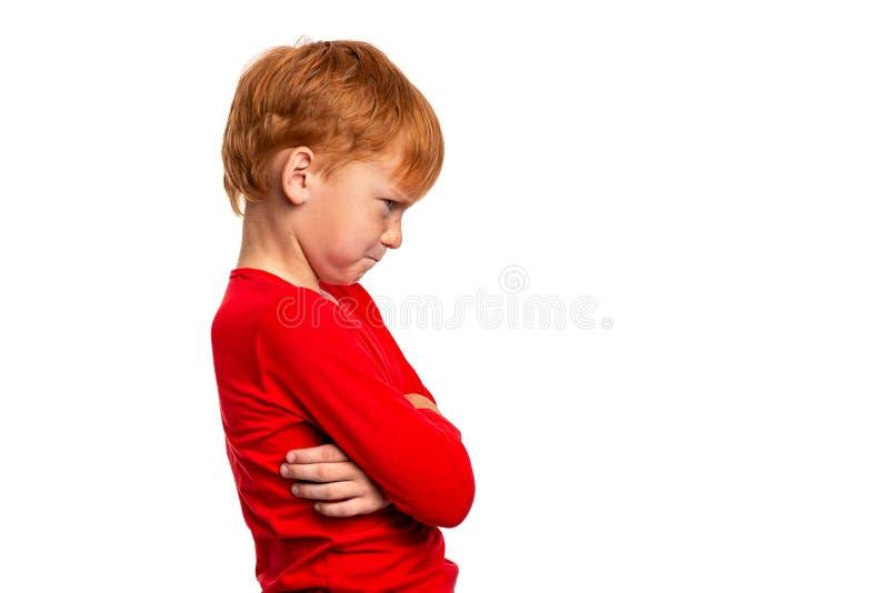 Taille vers le haut du portrait émotif des bras roux de profil de position de garçon croisés et regardants en colère de côté, d'i photographie stock