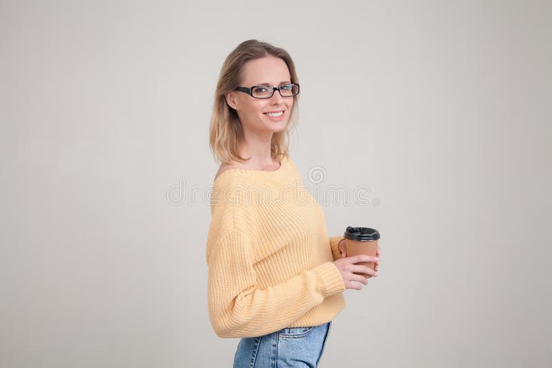 Taillen-obenportr?t von Blondinen Kaffeekappe in ihren H?nden halten und l?chelnd, die Kamera betrachtend tragende gelbe Strickja stockfoto