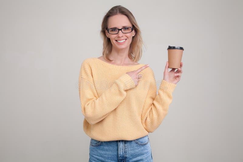 Taillen-obenportr?t von Blondinen Kaffeekappe in ihren H?nden halten und l?chelnd, die Kamera betrachtend und zeigen auf den Kaff lizenzfreies stockfoto