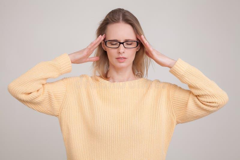Taillen-obenportr?t des Blondineh?ndchenhaltens auf Kopf, Kopfschmerzen habend tragende gelbe Strickjacke und Gl?ser Haltungen ge lizenzfreie stockbilder