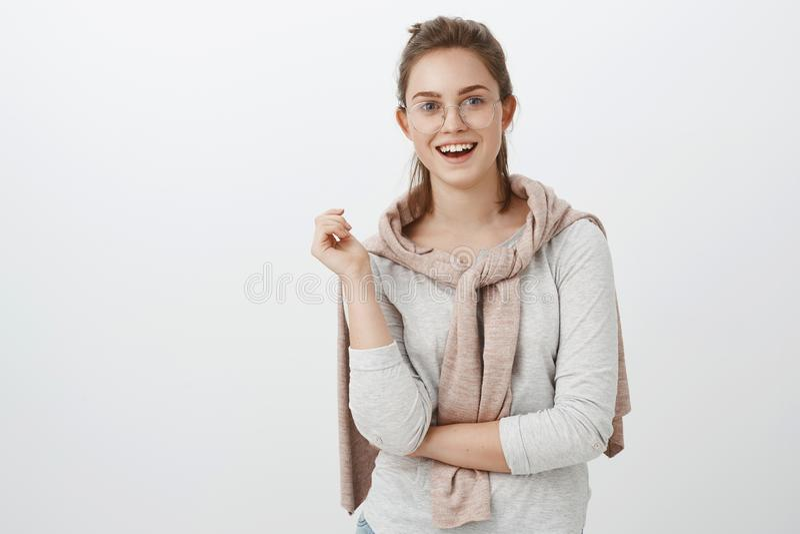 Taillen-obenschuß der unterhaltenen geselligen schönen europäischen Frau mit dem gekämmten Haar in den Gläsern und in Pullover ge lizenzfreie stockbilder