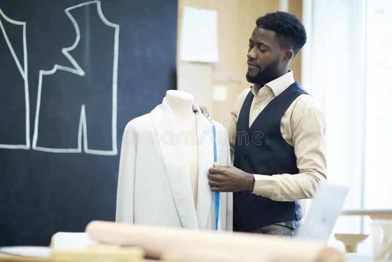 Tailleur beau sérieux travaillant sur la conception de veste photographie stock