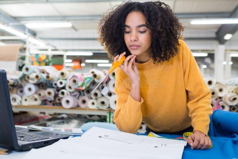 Tailleur de femme travaillant sur la nouvelle conception d'habillement photo libre de droits
