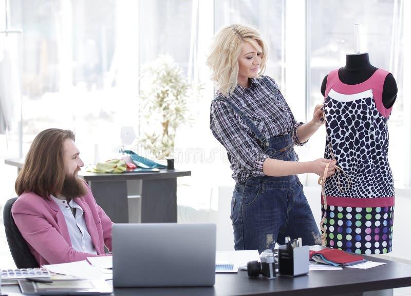 Tailleur et deux couturiers discutant des conceptions des nouveaux mod?les photos libres de droits